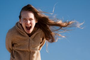 girl screaming with her hair blown sideways by the wind