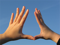 photo of hands against the sky with fingers spread