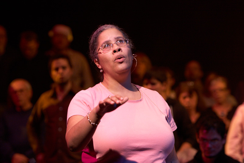 Sarah standing in front of seated choir members